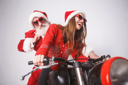 Happy young mrs. Claus wearing Santa hat, red sweater and sunglasses laughing while riding with Santa Claus on a motorcycle on the high speed, New Year, Christmas, holidays, souvenirs, gifts, shopping, discounts, shops, Snow Maiden Santa Claus,make-up, hairstyle, carnival.
