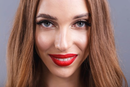 Portrait of attractive romantic long haired woman with red lips wearing black dress standing and smiling on the gray background, New Year, Christmas, holidays, souvenirs, gifts, shopping, discounts, shops, Snow Maiden Santa Claus,make-up, hairstyle, carnival.