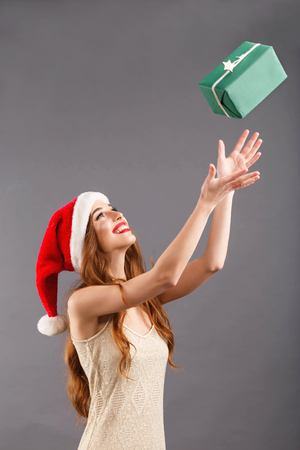 Fancy long haired woman in red santa claus hat with red lips standing on the gray background and tossing a present box in green packaging, New Year, Christmas, holidays, souvenirs, gifts, shopping, discounts, shops, Snow Maiden Santa Claus,make-up, hairstyle, carnival.