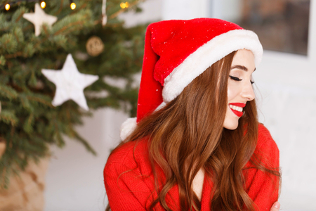 Portrait of attractive christmas woman wearing Santa hat and red sweater sitting on the floor near the cozy new year spruce, New Year, Christmas, holidays, souvenirs, gifts, shopping, discounts, shops, Snow Maiden Santa Claus,make-up, hairstyle, carnival.