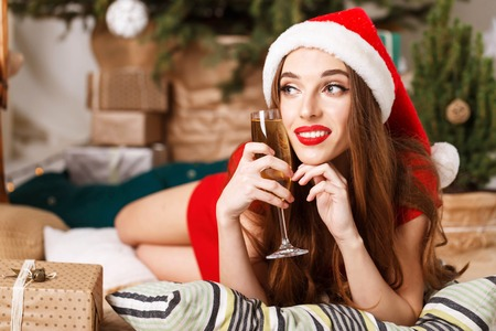 Hilarious christmas woman wearing Santa hat and red dress laying on the floor near the new year spruce with glass of champagne, New Year, Christmas, holidays, souvenirs, gifts, shopping, discounts, shops, Snow Maiden Santa Claus,make-up, hairstyle, carnival.
