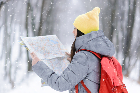 Brunette girl wearing grey jacket and yellow hat considers a map while walking with backpack in the winter snowy forest