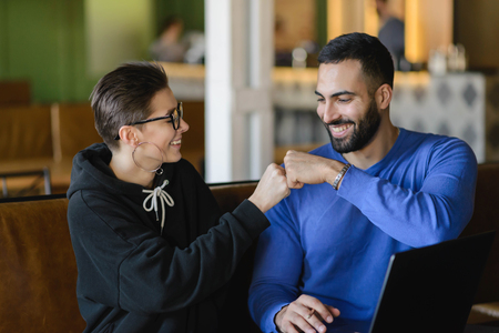 Cheerful shorthair woman bumping fist with male colleague making agreement cooperating on homework