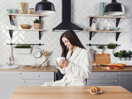Long haired woman sitting with the cup of coffe at the light modern kitchen 版權商用圖片
