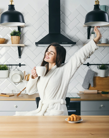 Young woman stretching at the kitchen while having her morning coffee