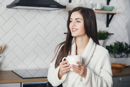 Young girl in white bathrobe standing with the cup of coffe and looking to the window