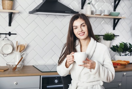 Portrait of brunette girl sitting with the cup of coffe at the kitchen 版權商用圖片