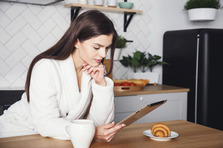 Longhaired woman using digital tablet in kitchen at home