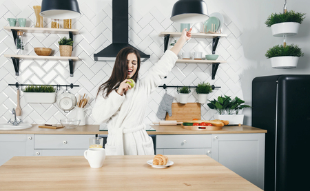 Brunette woman in white bathrobe sing a song to the apple like a microfon at the kitchen