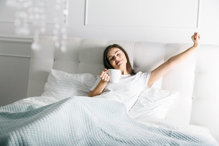 Attractive woman stretching in the bed at the morning
