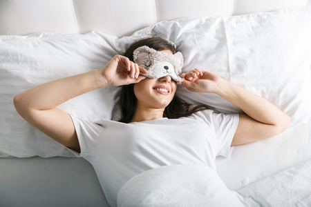 Brunnette woman in cute teddy mask on face waking up in her bedroom