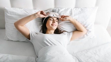 Woman takes off her mask while she waking up