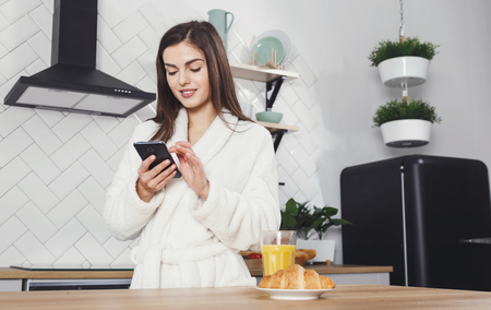 Beautiful girl in a white bathrobe using smartphone during drinking juice