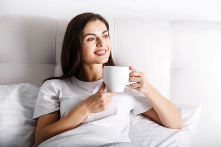 Happy young woman with cup of coffee or tea in bed at home bedroom 免版税图像