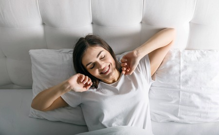 Cute woman waking up at her white bed