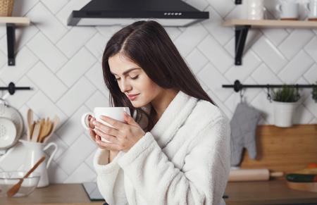 Young brunette girl inhales the aroma of coffee at the morning kitchen