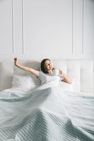 Attractive woman stretching at the bed in the morning 版權商用圖片
