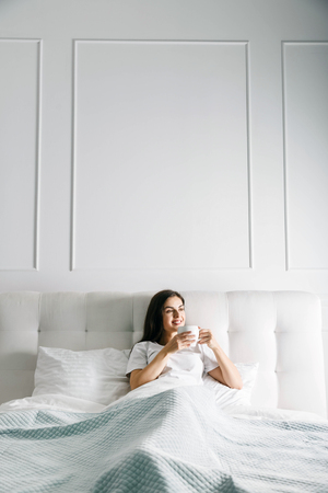 Cute girl laying with the cup of coffe at the bed
