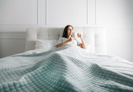 Longhaired woman laying at the bedroom with the cup of coffee