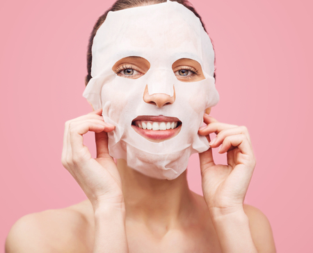 Beautiful young woman is applying a cosmetic tissue mask on a face on a pink background