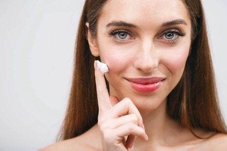Young woman applying moisturizing lotion cosmetic cream on face for clean healthy soft skin care