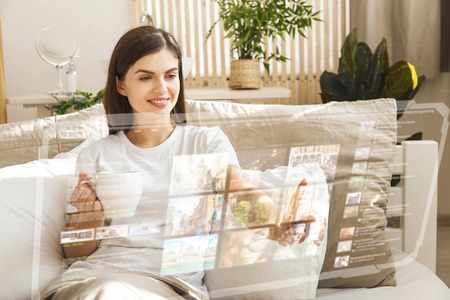 Cheerful girl using futuristic hologram panel in the bedroom in the sunny morning 版權商用圖片