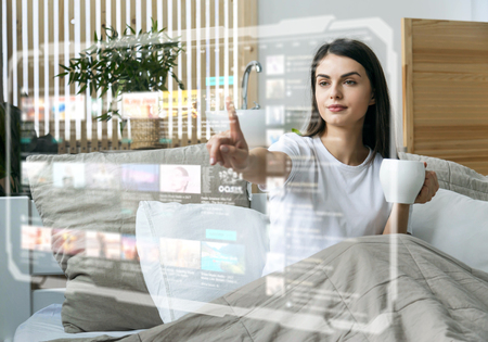 Beautiful girl uses hologram futuristic panel touch screen for watching videos holding cup of coffee in the bedroom