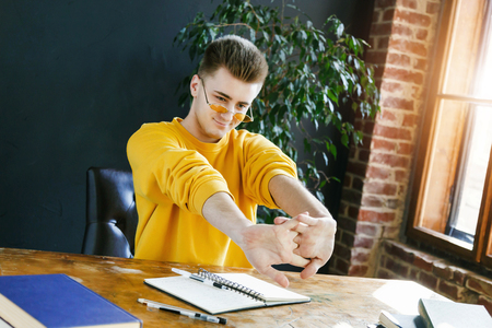 Blonde student in glasses wearing yellow pullover stretching his hands while preparing for test or exam