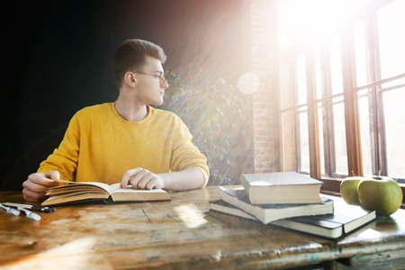 Blonde student in glasses wearing yellow pullover looking to the window while doing his homework at the class