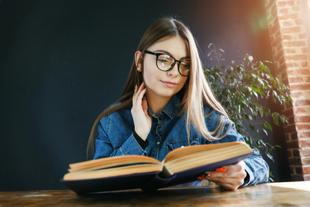 Longhaired student girl wearing glasses doing his homework at the wooden table