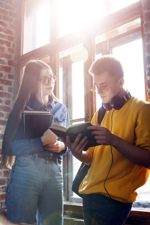 Two teen students chatting while standing near big window