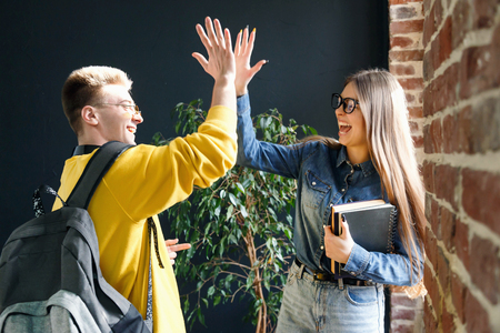 Young cheerful students giving five to each other