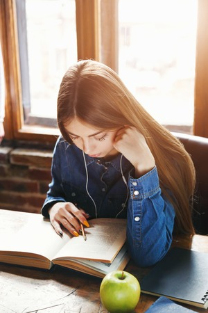 Brunette smiling student girl sitting at the desk listening music and reading book