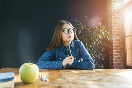 Brunette student girl wearing glasses holding pencil and looking to the window 版權商用圖片