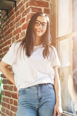 Brunette longhaired woman in white t-shirt and jeans wearing glasses standing near the window and brick wall 版權商用圖片