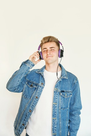 Teen blonde man wearing white t-shirt and jeans jacket listening music in big headphones at the white background 版權商用圖片