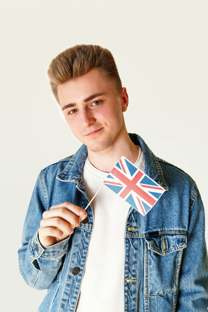 Teen blonde man wearing white t-shirt and jeans jacket holding small flag of England while standing on the white background