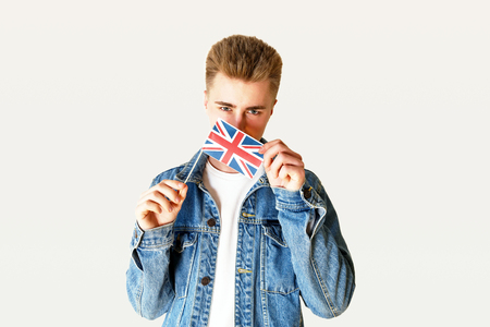 Teen blonde man wearing white t-shirt and jeans jacket showing small flag of England while standing on the white background