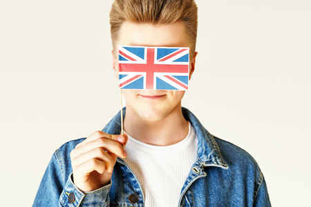 Portrait of teen blonde man wearing white t-shirt and jeans jacket hides his face behind the small flag of England while standing on the white background.