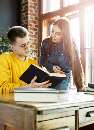 Blonde student in glasses wearing yellow pullover studying at the class with a friend 版權商用圖片