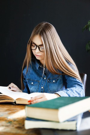 Student long haired girl wearing glasses sitting by wooden table and reading book 版權商用圖片