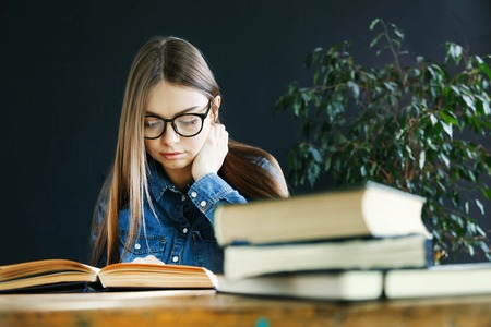 Longhaired student girl wearing glasses sitting by wooden table and preparing to the exams 版權商用圖片