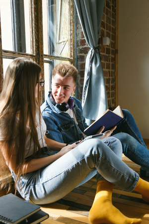 Two teen classmates talking with each other while holding electronic and paper books