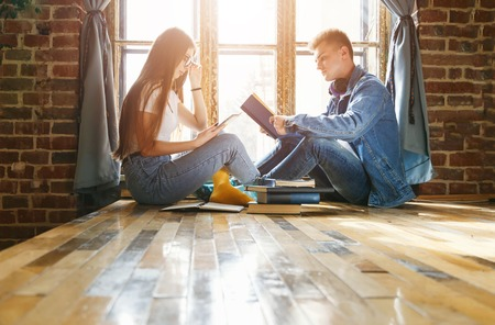 Blonde teen boy reading book and his classmate brunette girl watching something on the tablet 版權商用圖片