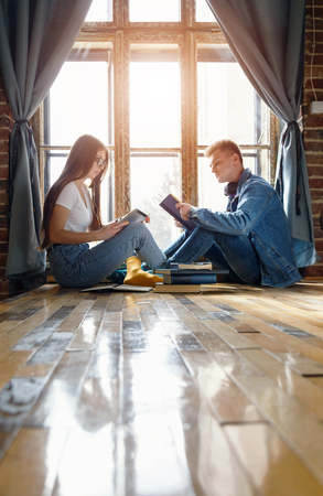 Blonde teen boy and brunette girl reading book and watching something on the tablet