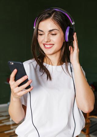 Brunette longhaired woman wearing white t-shirt listening her favorite songs