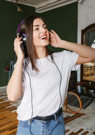 Brunette longhaired woman in headphones wearing white t-shirt enjoying her favorite music 版權商用圖片