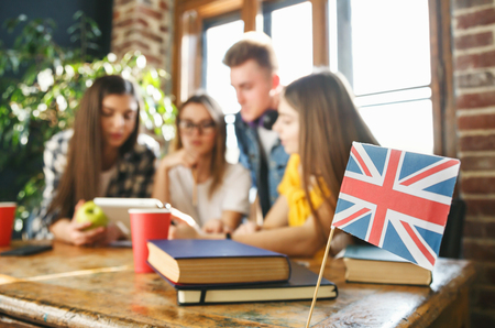 Group of classmates sitting at the desk, looking at the tablet and discussing something, camera focused on the british flag 版權商用圖片 - 121262436