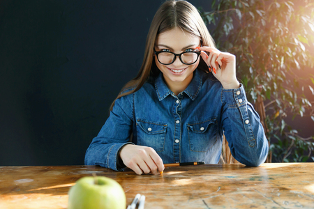 Brunette smiling student girl in jeans shirt sitting at the desk and looking out of glasses 版權商用圖片