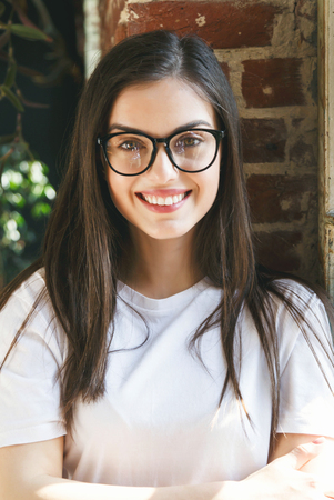 Brunette longhaired woman wearing glasses smiling near the window and brick wall